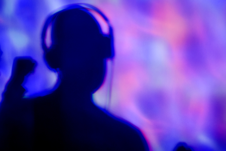 vj: the silhouette of a young man wearing headphones in a dance club with colorful lights