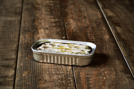 sardine can: an open sardine can on a rustic wooden surface