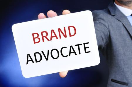 それで書かれたテキストのブランド支持者の看板を示すグレーのスーツの若い白人ビジネスマンのクローズ アップ 写真素材