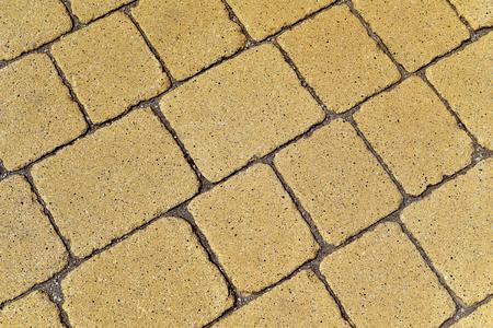 stonemasonry: closeup of a yellow stone wall or a stone pavement background in diagonal Stock Photo