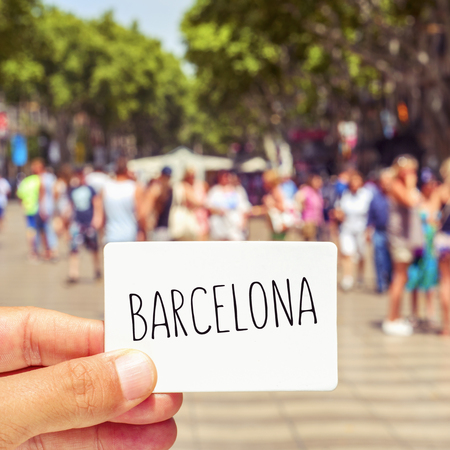 ramblas: closeup of the hand of a young man showing a signboard with the word Barcelona, at the famous Las Ramblas in Barcelona, Spain