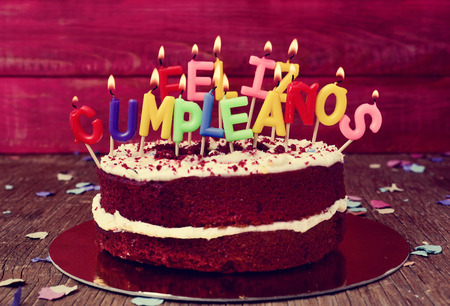of yesteryear: a cake topped with some lit letter-shaped candles forming the text feliz cumpleanos, happy birthday in Spanish, before blowing out the cake, on a rustic wooden table Stock Photo