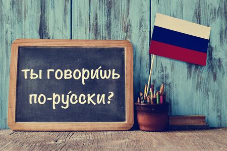 黒板の質問にロシア語を話すか?木製の机の上、ロシア語で鉛筆、いくつかの本、ロシアの国旗とポット書かれて
