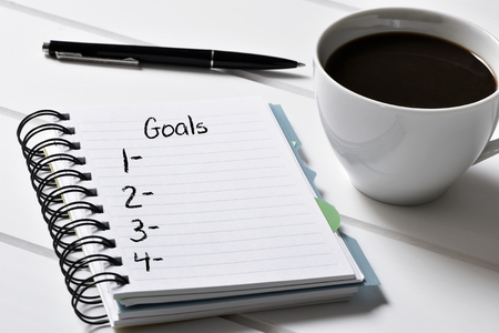 closeup of a notebook with a blank list of goals and a cup of coffee on a white wooden table Stok Fotoğraf - 51014827