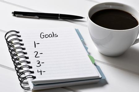 metas: primer plano de un cuaderno con una lista en blanco de los objetivos y una taza de café en una mesa de madera blanca Foto de archivo