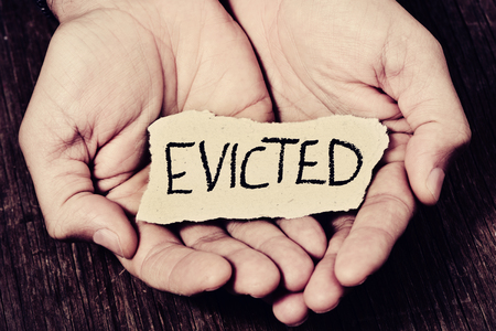 indigent: closeup of a piece of paper with the word evicted in the hands of a caucasian man