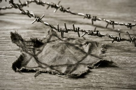 remembrance day: closeup of a Jewish badge and barbed wire on a rustic background, in sepia toning