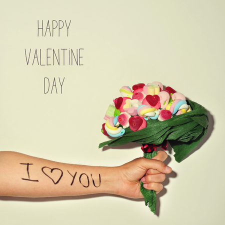i love you sign: closeup of a young man offering a candy bouquet with the sentence I love you written in his forearm, and the text happy valentines day
