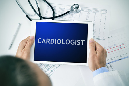 ventricles: closeup of a doctor man sitting at his office desk holding a tablet computer with the word cardiologist in its screen