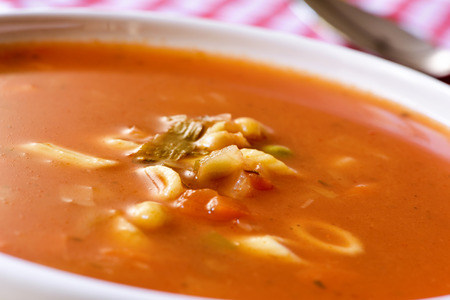 minestrone: closeup of a bowl with minestrone, a typical italian soup, with vegetables and pasta