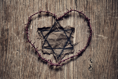 persecution: closeup of a Jewish badge and barbed wire forming a heart on a rustic surface, in memory of the victims of the Holocaust