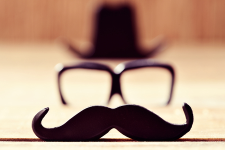 a mustache, a pair of eyeglasses and a black hat placed in different levels forming the face of a gentleman Stock Photo