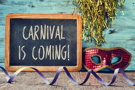 mardi gras mask: an elegant red and golden mask, a chalkboard with the text carnival is coming and a streamer on a rustic wooden surface