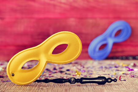 handled: two handled carnival masks, one yellow and one blue, and confetti of different colors on a rustic wooden surface, against a rustic red background