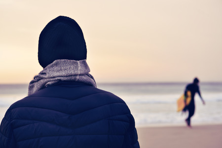 knit cap: closeup of a young caucasian man seen from behind wearing scarf, a knit cap and a coat in front of the ocean, and a surfer carrying his surfboard in the background Stock Photo