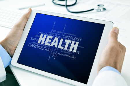 endocrinology: closeup of a doctor man sitting at his office desk holding a tablet computer with a tag cloud about health in its screen