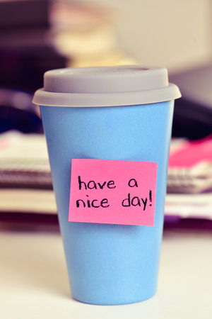 courtesy: a pink sticky note with the text have a nice day attached to a blue cup of coffee or tea on an office desk Stock Photo