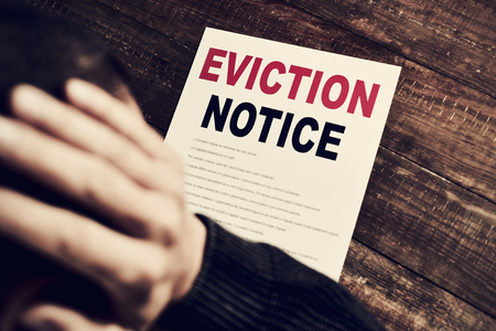 a young caucasian man with his hands in his head concerned because has just received an eviction notice Standard-Bild