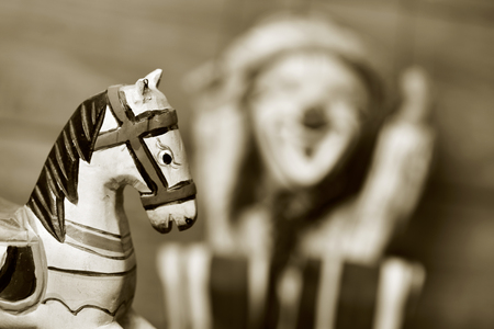 of yesteryear: closeup of an old wooden horse and an old marionette in the background, in sepia toning