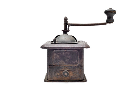 antique background: an old and rusty manual burr-mill coffee grinder on a white background Stock Photo