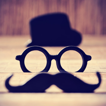 a mustache, a pair of eyeglasses and a black hat placed in different levels forming the face of a gentleman