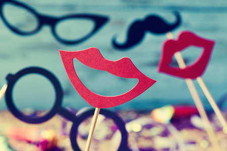 mustaches: some different mouths, eyeglasses and mustaches on sticks, against a blue background and a wooden surface full of confetti