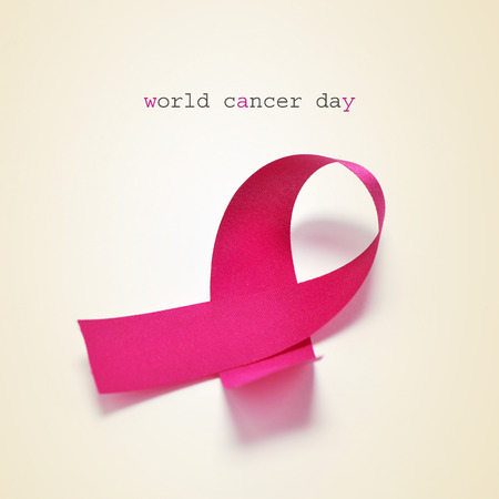 the text world cancer day and a pink ribbon on a beige background Stock Photo