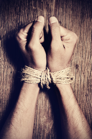 nonconformity: high-angle shot of the hands of a young man tied with rope on a rustic wooden table, as a symbol of oppression or repression, with a dramatic effect