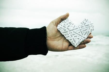 telegrama: Primer plano de la mano de un hombre joven sosteniendo un corazón maquillada con tiras de papel con el día de San Valentín feliz de texto, con una viñeta añadido