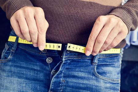 체중 증가 때문에 벨트로 측정 테이프가있는 청년이 바지를 입으려고합니다.