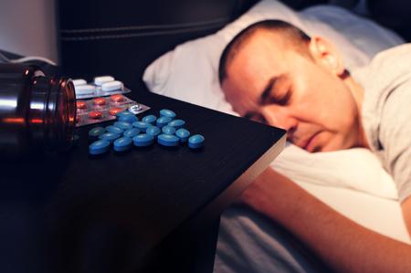 ナイト テーブルで若い男が彼の目とベッドに顔を敷設いくつかの別の薬のクローズ アップは、夜間閉鎖 写真素材