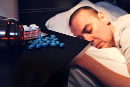 sleep: closeup of some different pills in the nightstand and a young man laying face down in bed with his eyes closed, at night Stock Photo