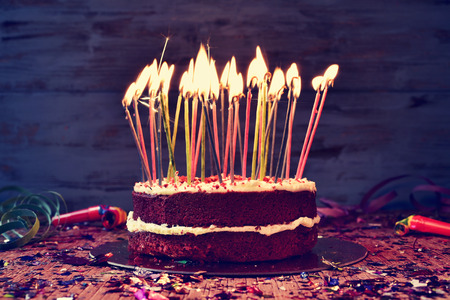 happy birthday candles: a cake topped with some lit candles before blowing out the cake, on a rustic wooden table full of confetti, party horns and streamers, with a filtered effect