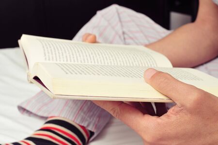prose: closeup of a young caucasian man wearing pajamas and colorful striped socks reading a book in bed Stock Photo