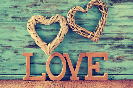 heart background: two heart-shaped ornaments made with natural fibers and some wooden letters forming the word love, against a blue rustic wooden background Stock Photo