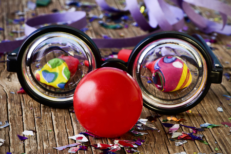 nearsighted: a pair of fake short-sighted eyeglasses and a red clown nose, on a rustic wooden surface full of confetti, party horns and streamers