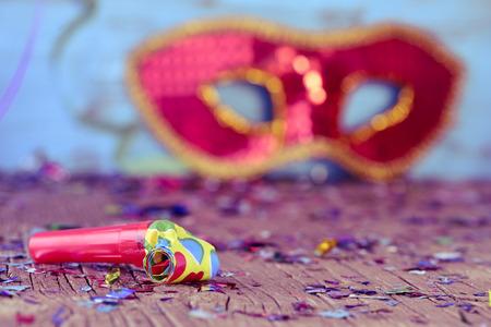 Nahaufnahme einer Partei Horn auf eine rustikale hölzerne Oberfläche voller Konfetti und eine elegante roten und goldenen Karneval Maske im Hintergrund