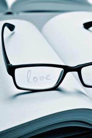 duotone: the word love handwritten in a notebook seen through the lens of a black plastic-rimmed eyeglasses, in duotone