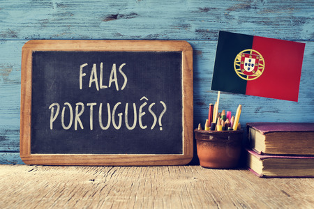 speaking: a chalkboard with the question question falas portuges? do you speak Portuguese? written in Portugese, a pot with pencils, some books and the flag of Portugal, on a wooden desk