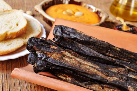 calsotada: closeup of some barbecued calcots, sweet onions, served in a tile and a bowl with romesco sauce, typical of Catalonia, Spain