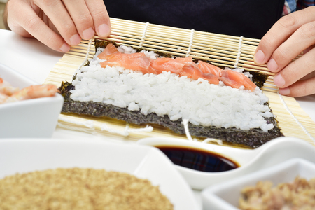 japanese cookery: closeup of a young man preparing makizushi, filled with tuna, on a table with bowls with different ingredients Stock Photo