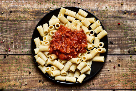 bolognese sauce: high angle shot of a black plate with penne rigate with bolognese sauce on a rustic wooden table