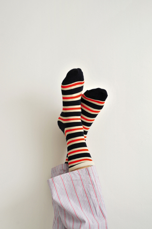 homeware: closeup of a young man in pajamas wearing colorful striped socks with his feet against the wall
