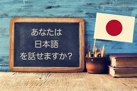 translation: a chalkboard with the question do you speak Japanese? written in Japanese, a pot with pencils, some books and the flag of Japan, on a wooden desk Stock Photo