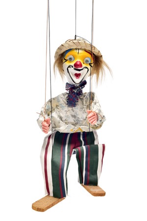 puppetry: an old marionette with its face painted like a clown being manipulated against a white background Stock Photo