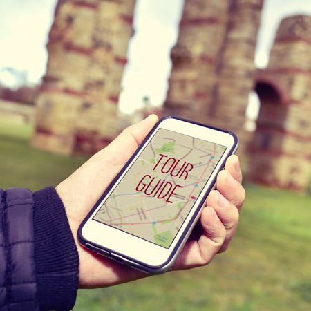 tour guide: closeup of a young caucasian man with a smartphone with the text tour guide in its screen, in front of some ancient architectural remains Stock Photo