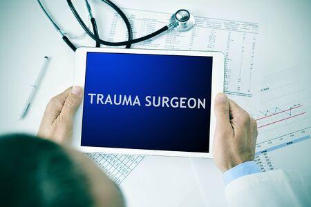cirujano: Primer plano de un hombre médico sentado en su escritorio de oficina con un tablet PC con el cirujano de trauma texto en su pantalla