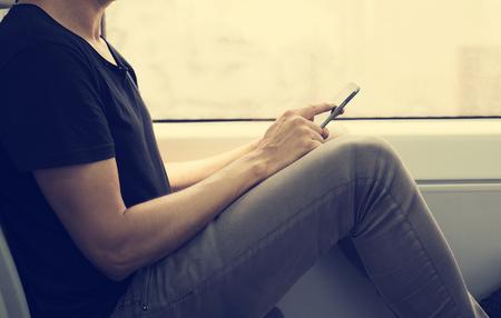 tren: primer plano de un hombre caucásico joven usando un teléfono inteligente en un tren o el metro