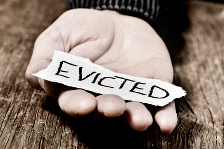 indigent: closeup of a piece of paper with the word evicted in the hand of a caucasian man