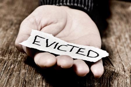hombre pobre: primer plano de un trozo de papel con la palabra desalojado en la mano de un hombre caucásico